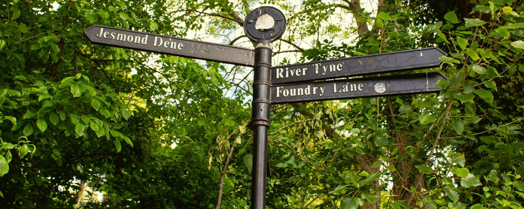 Street sign in Ouseburn pointing to Foundry Lane, RIver Tyne and Jesmond Dene