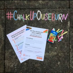 Photo of chalk up Ouseburn written on the ground next to a box of chalk and chalk art challenge poster